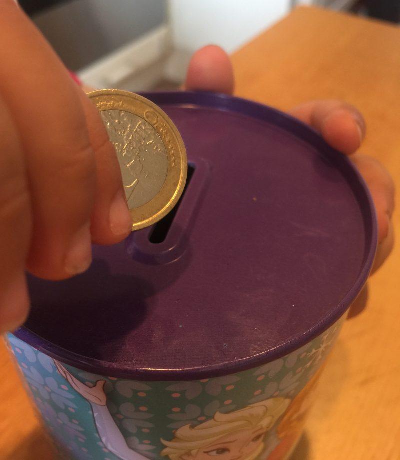 Spardose das von einem Kind befüllt wird symbolisch für den Zinseszins